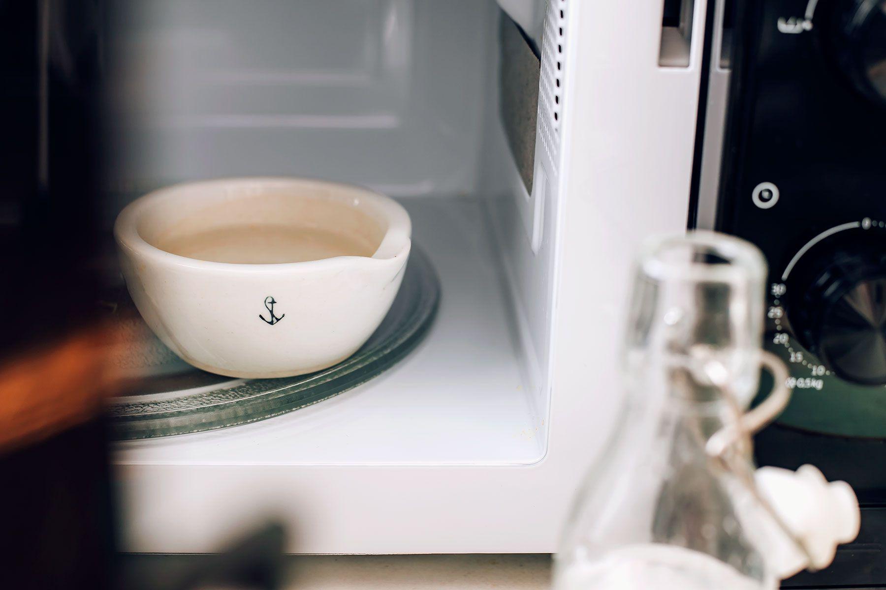 Distilled white vinegar in bowl being heated in microwave