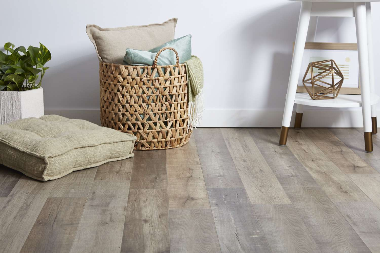 Laminate flooring with cushion, houseplant, woven basket with pillows and white stool