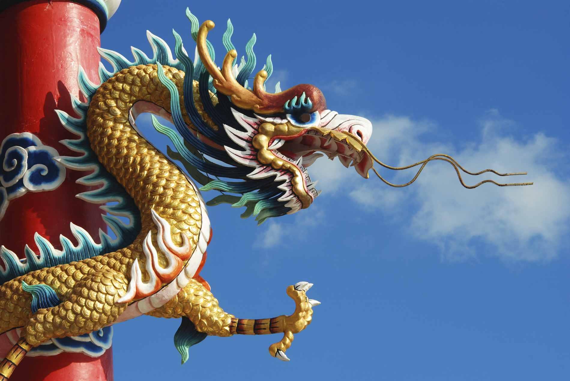 A dragon feng shui cure on a pole
