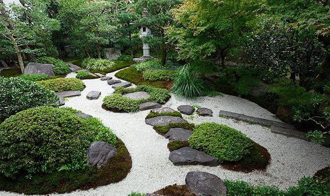 Stones and moss form a path through white gravel in a Japanese garden.