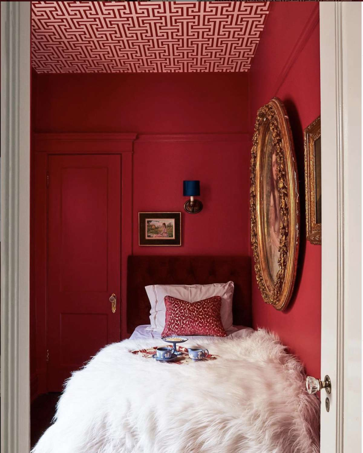 bedroom with red walls, red and white pattern ceiling, white fluffy blanket