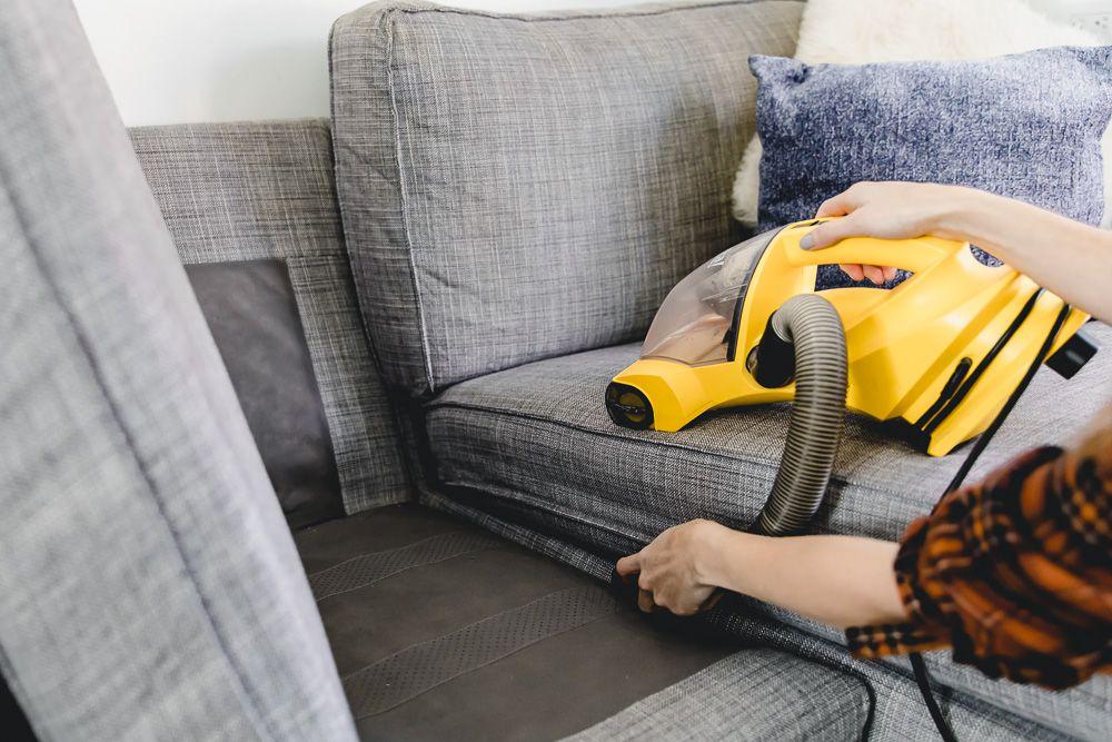 person vacuuming inside a sofa