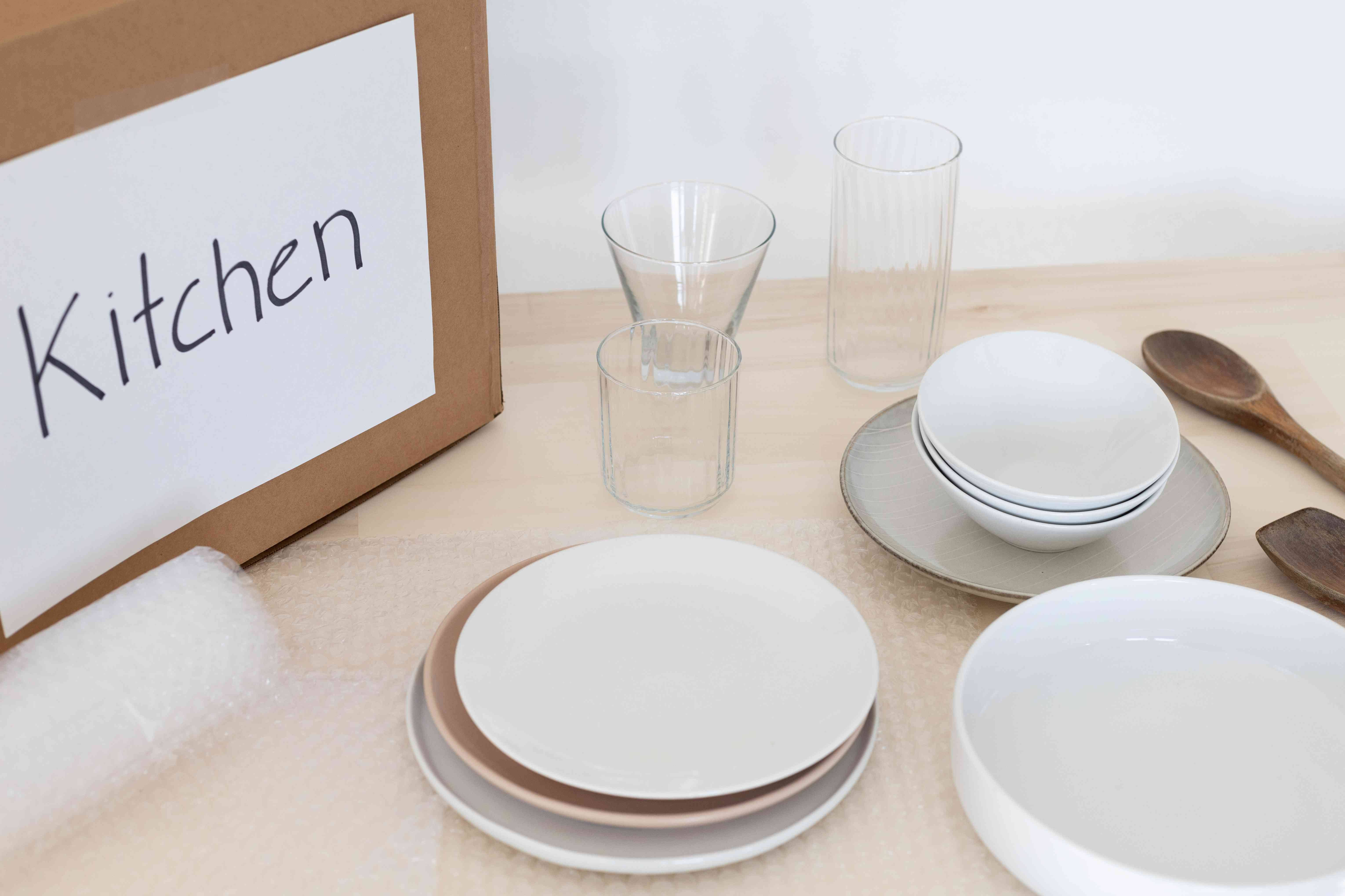 Bubble wrap under dining plates and glass cups next to labeled cardboard box marked kitchen