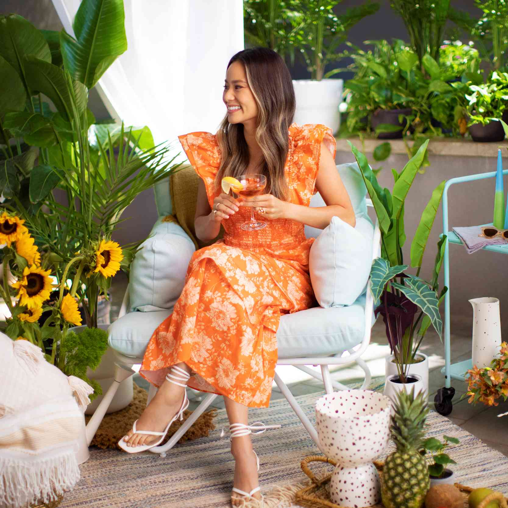 Jamie Chung poses on a mint green chair next to a mint green bar cart