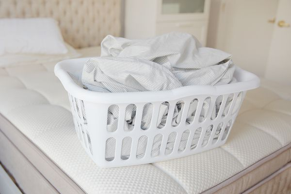 basket of laundry on a mattress