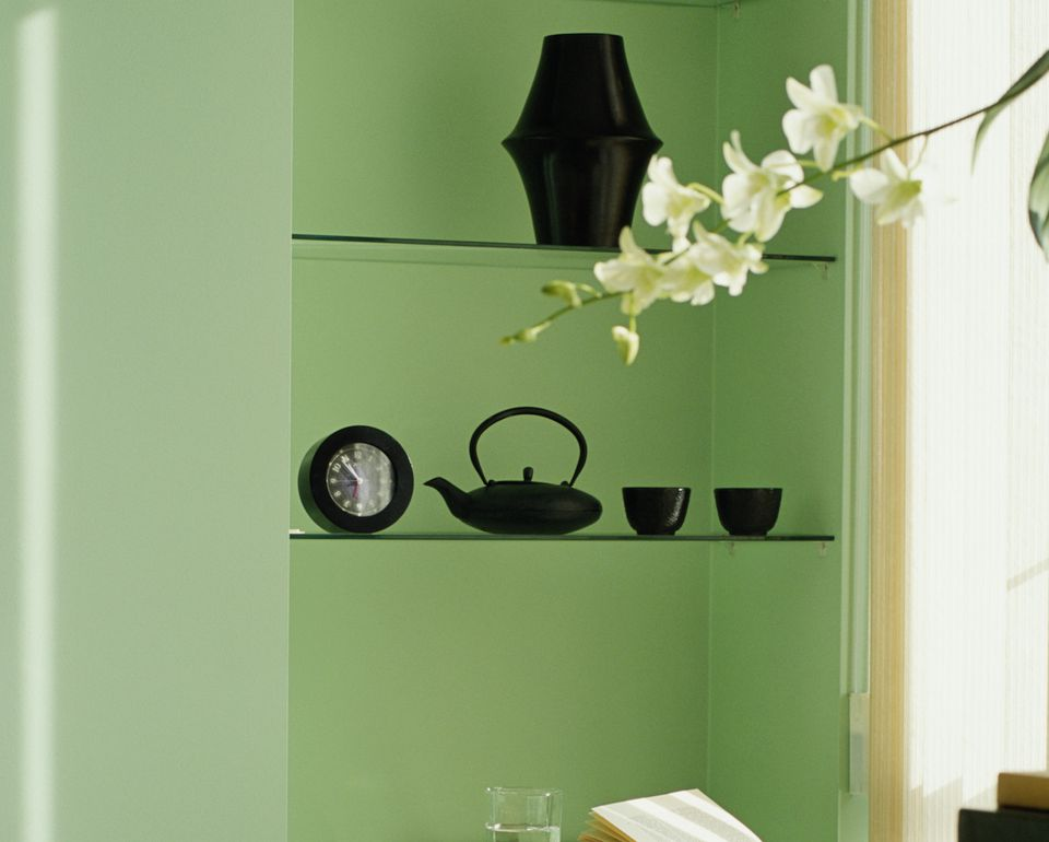 Green shelf with black clock, teapot, teacups, and vase