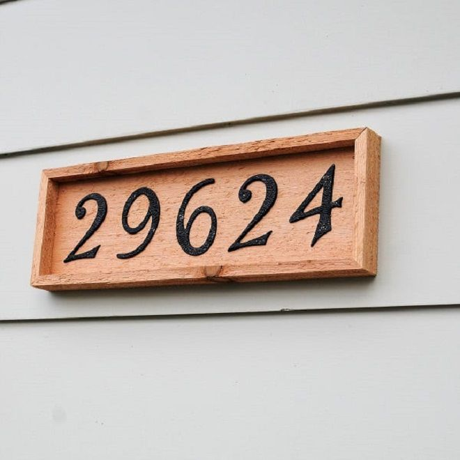 A wooden plaque with address numbers painted on.