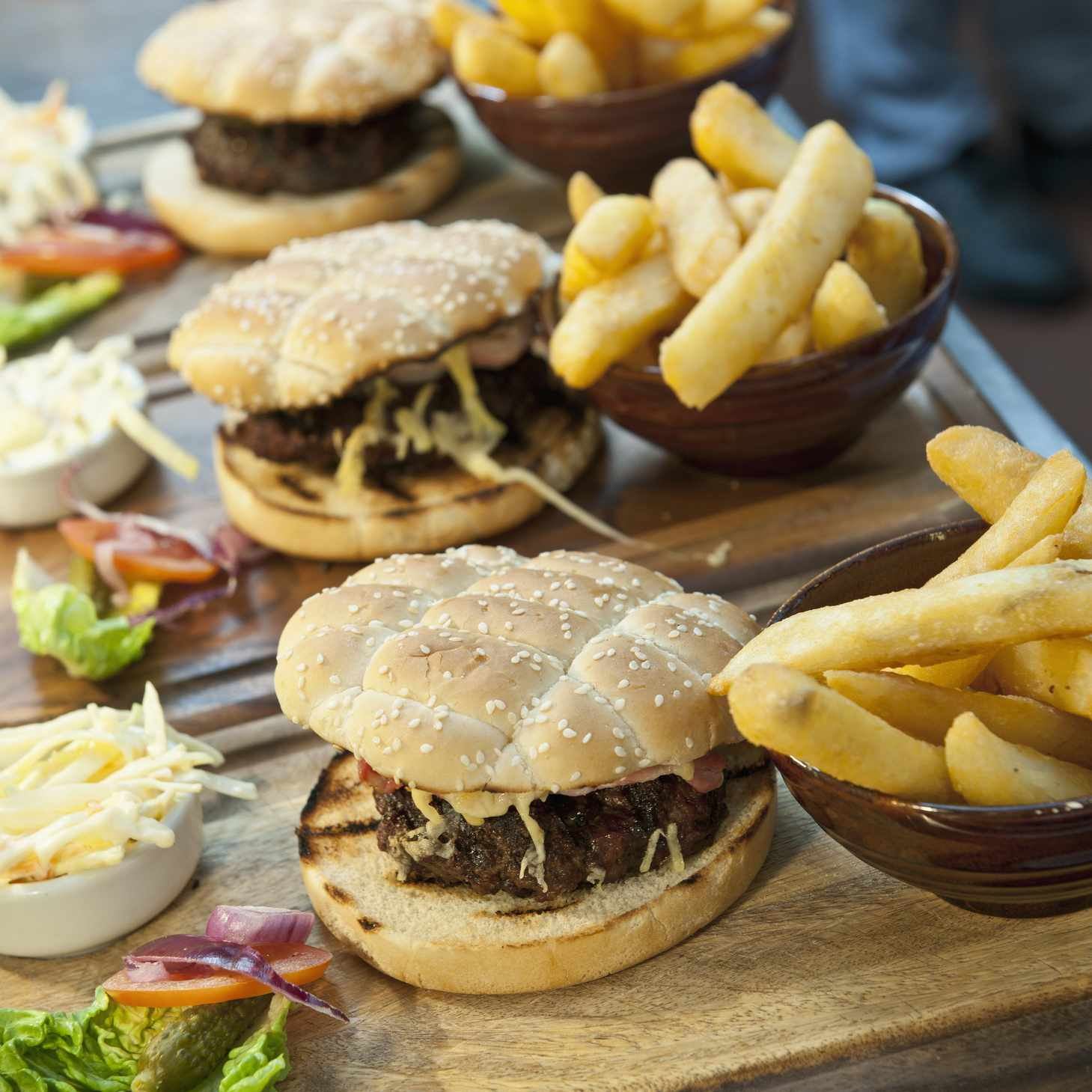 Three burger and fries on wooden trays..