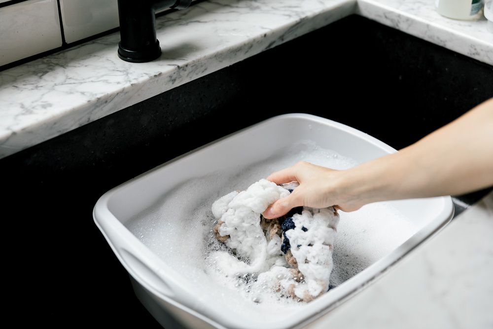 Someone submerging a crochet blanket into a washing vessel