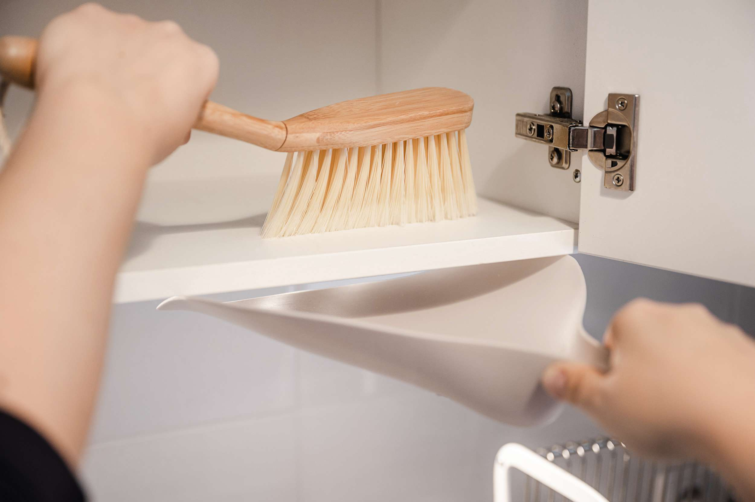 Bottom shelf of kitchen pantry swept by soft bristled brush and pan