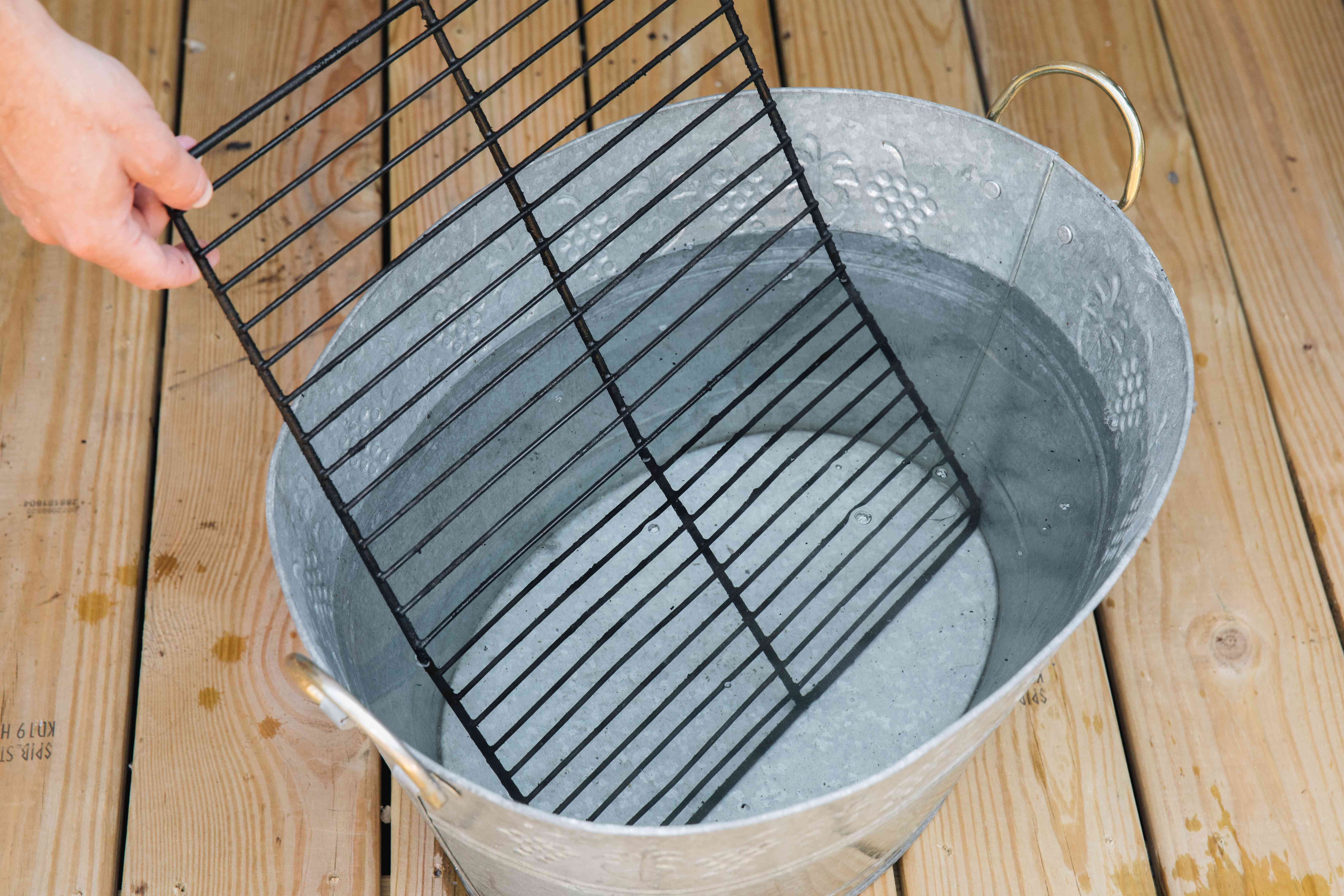 soaking grates in a basin with vinegar