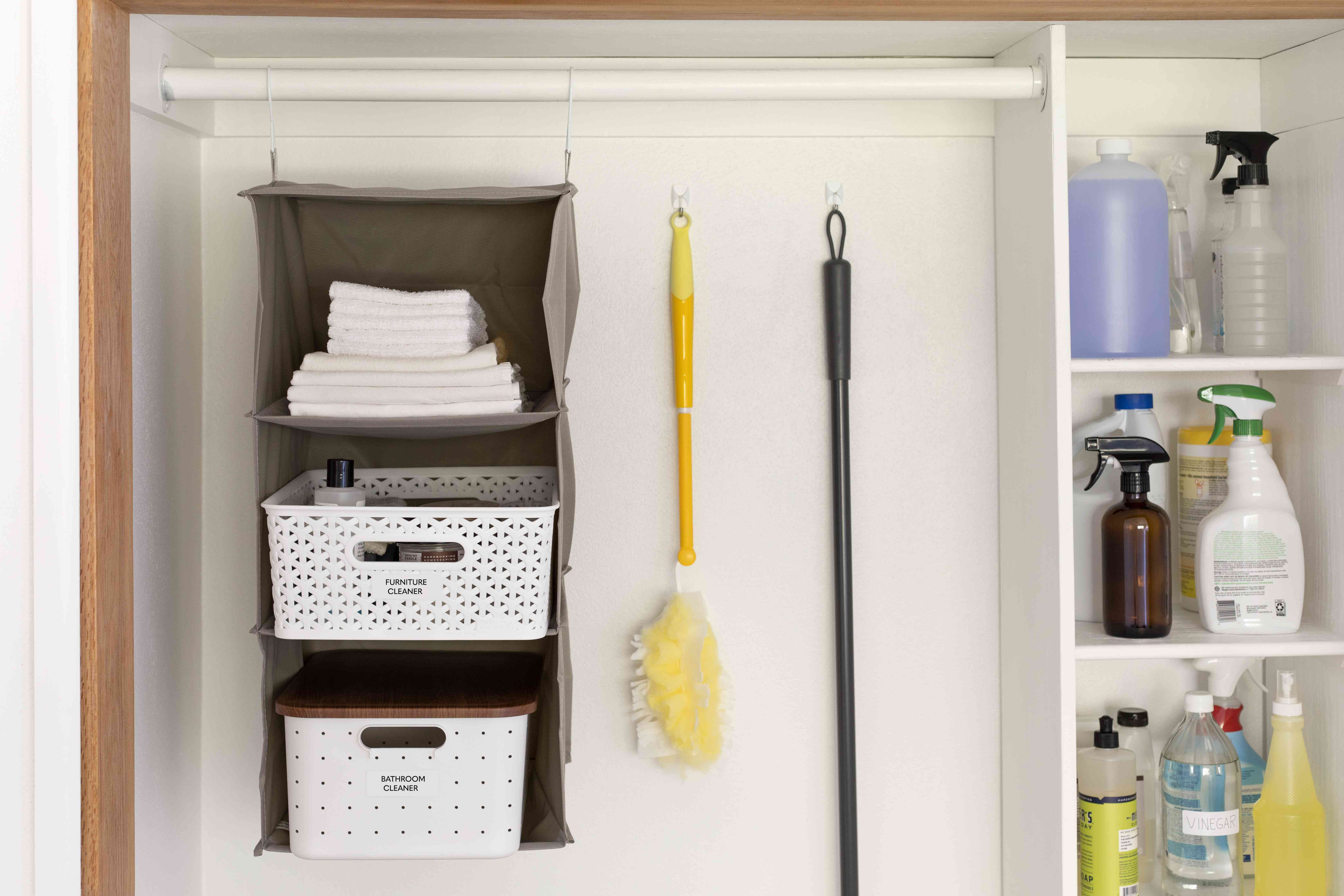 Hanging shelves inside closet with brush and broom hanging veritcally