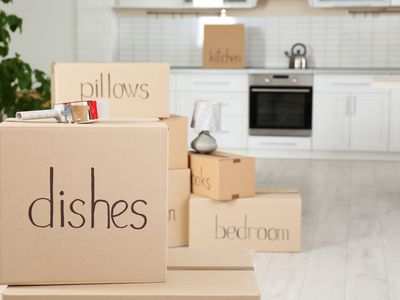Moving boxes and adhesive tape dispenser in kitchen. Space for text
