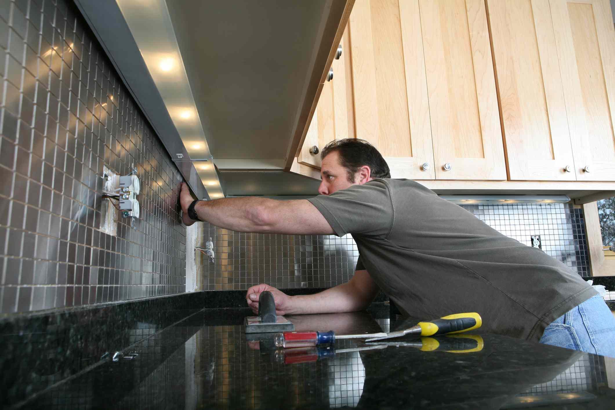 Man installing backsplash