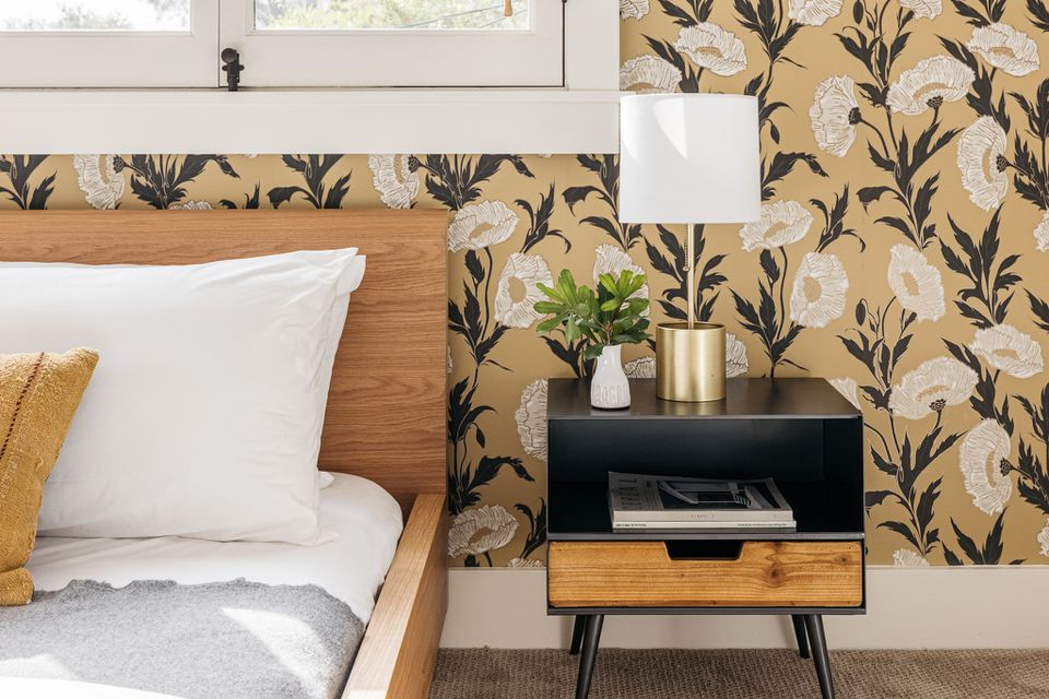 Decorated bedroom with floral wallpaper, black and wood nightstand and wood bed frame with white linens