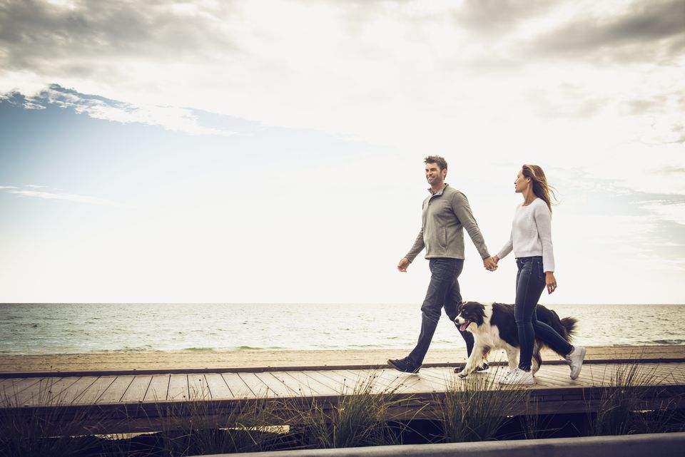 Caucasian couple walking on boardwalk with the dog