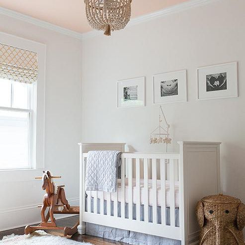Simple nursery with neutral tones and painted pink ceiling