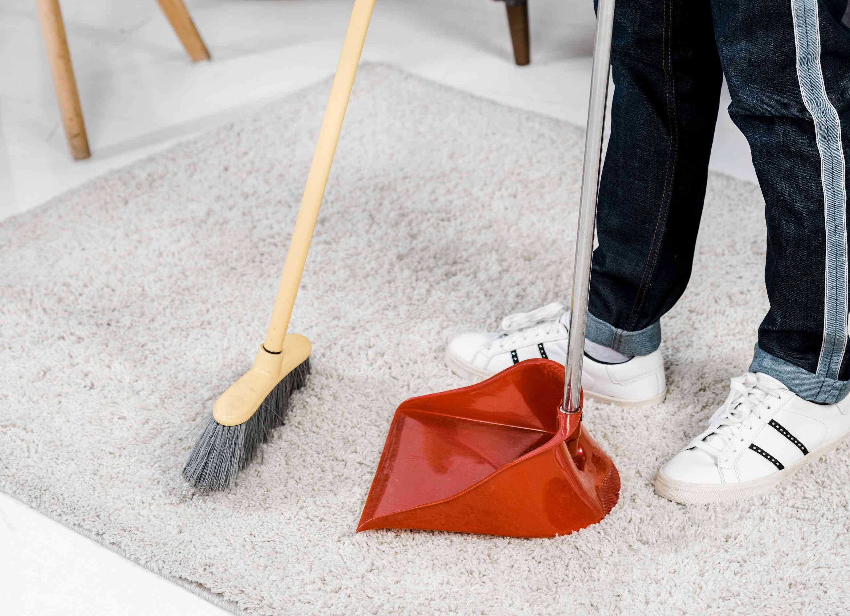 Person sweeping carpet with broom and dustpan