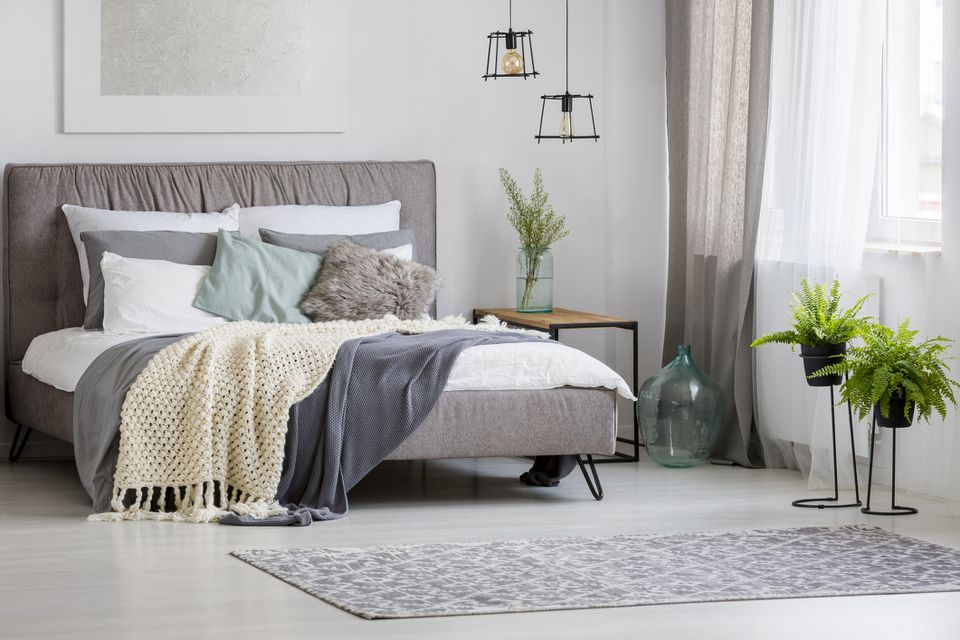 Grey, modern bedroom interior with king-size bed decorated with cushions and blankets