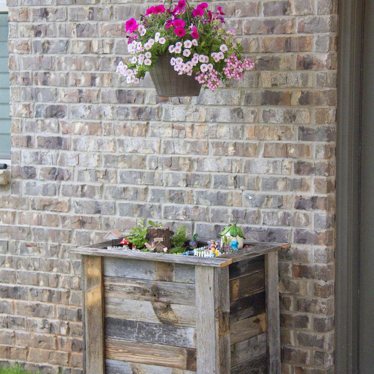 Macetero alto de madera recuperada con flores dentro y encima