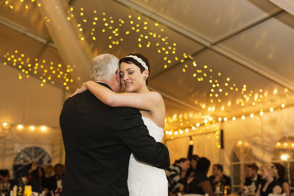 Bride dancing with father at reception with twinkle lights on the ceiling.