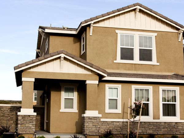 Brown stucco home with white trim