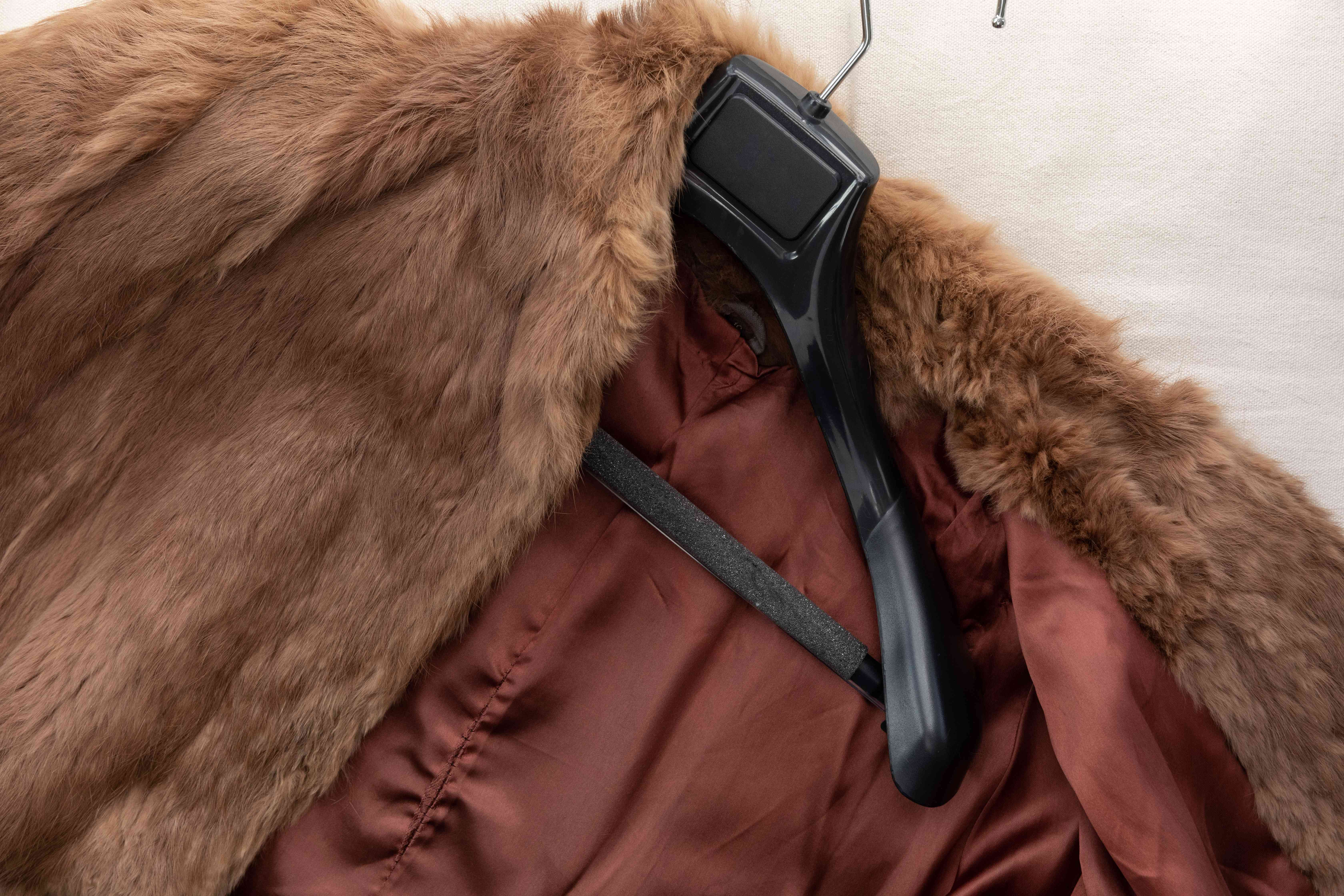 A brown fur coat on a sturdy hanger