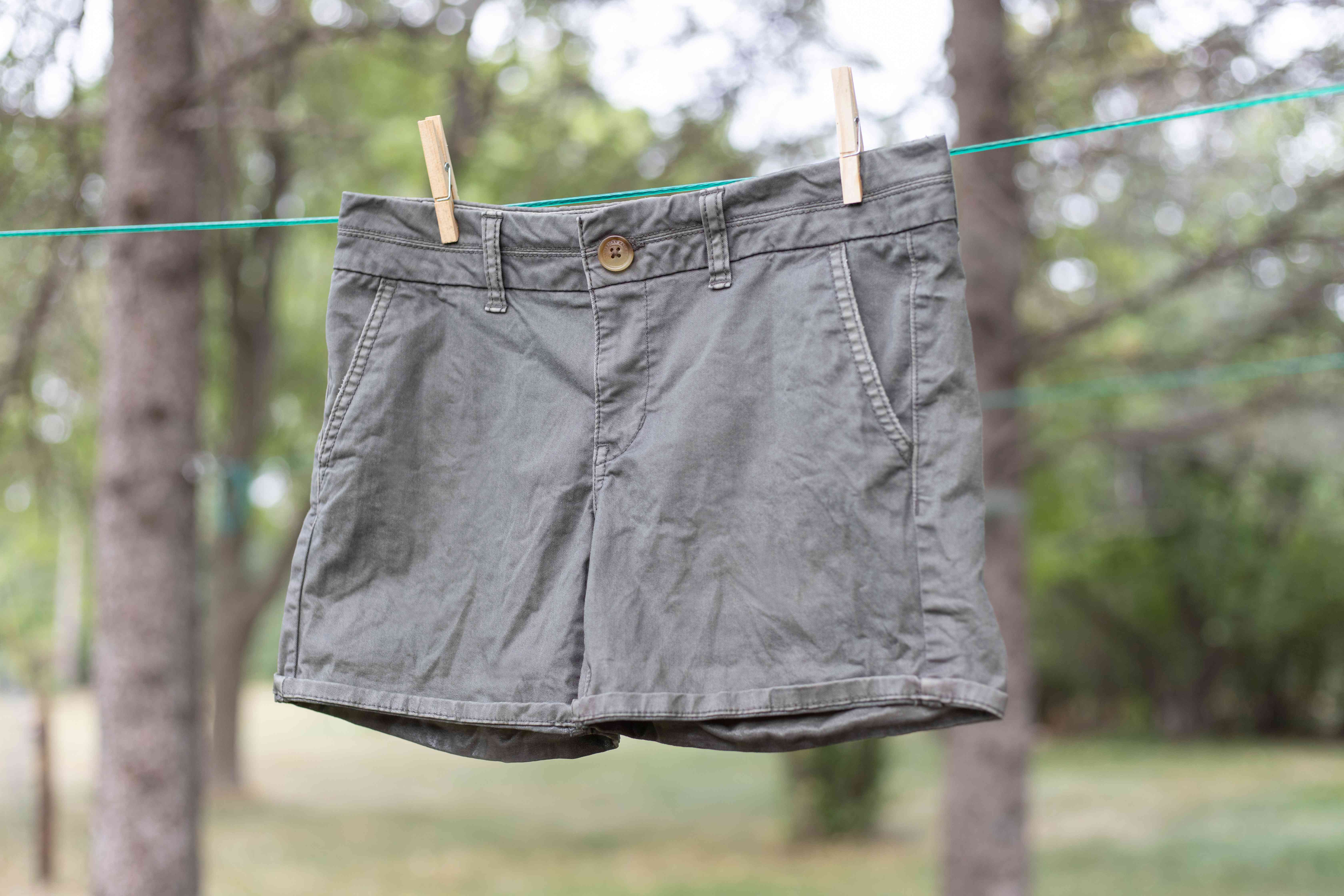 Cargo pants with skunk odor air drying on clothes line