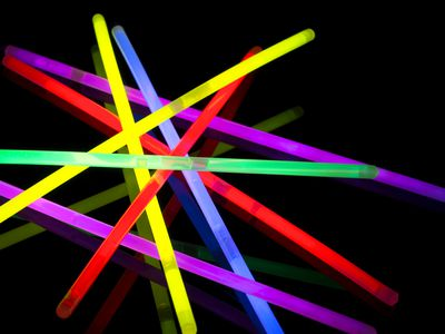 Glow sticks scattered on a black background