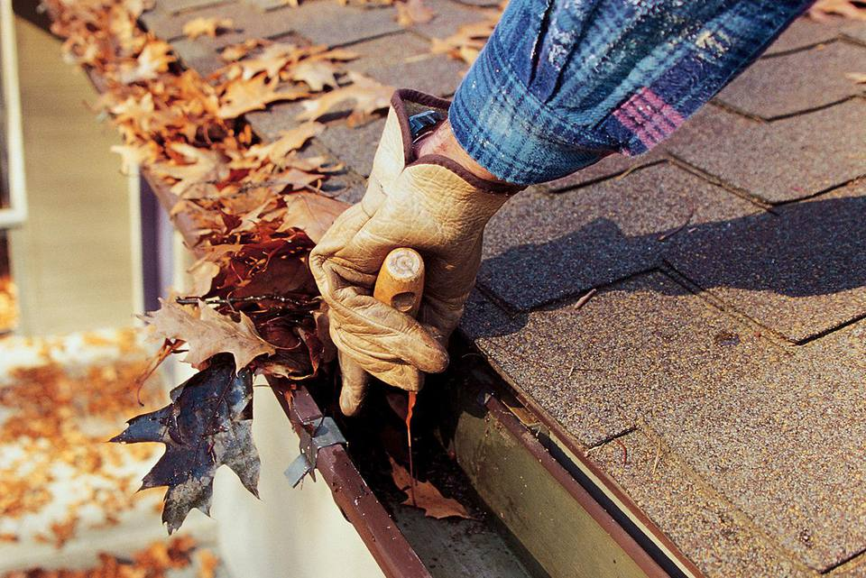 Person wearing gloves and using a tool to take leaves out of gutter.