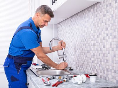a repairman working on a sink faucet
