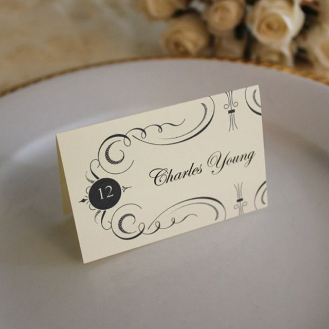 a cream and black wedding place card on a plate - Printed Wedding Place Cards