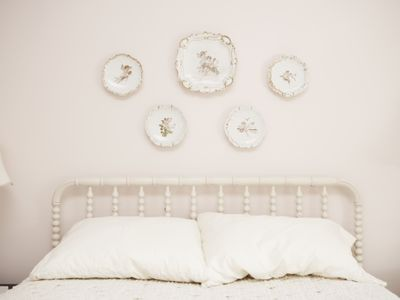 Bedroom with porcelain hanging on wall above bed