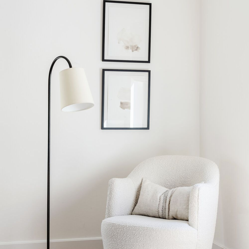 corner with white accent chair, modern lamp, simple artwork