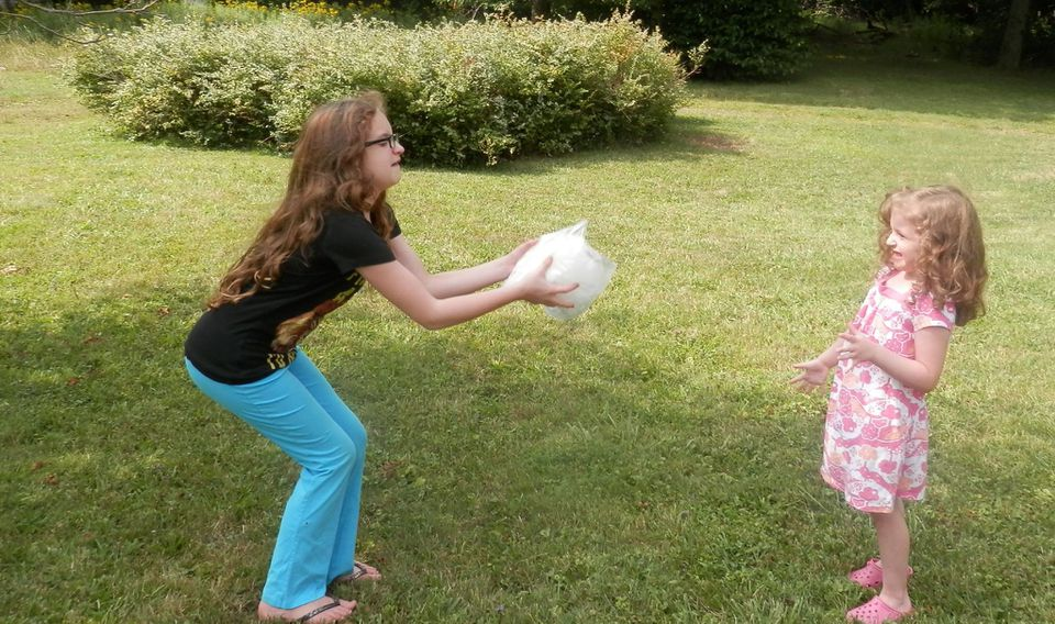 girl throwing bag of ice cream to younger girl