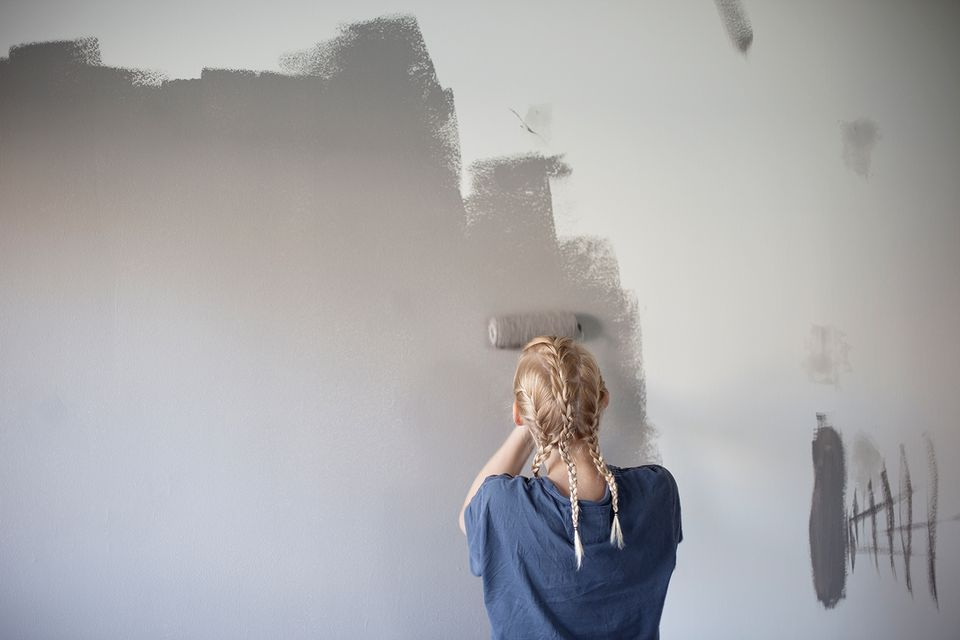 Rear view of girl painting wall
