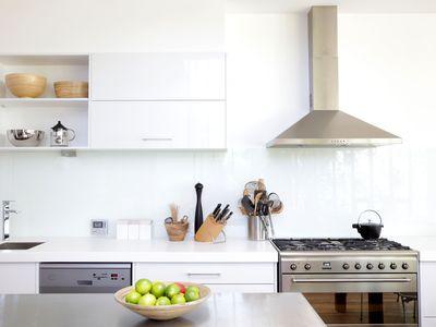 Minimalist white kitchen with stainless steel appliances