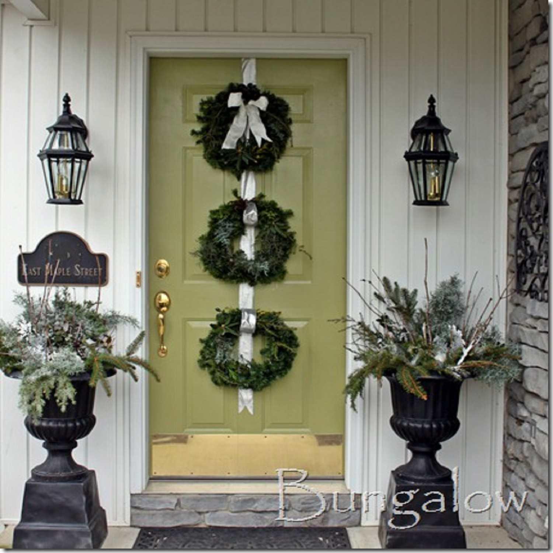 tres coronas de flores en una puerta de entrada