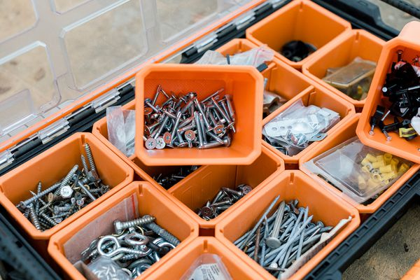 screws, nails, and other parts organized in a tool box