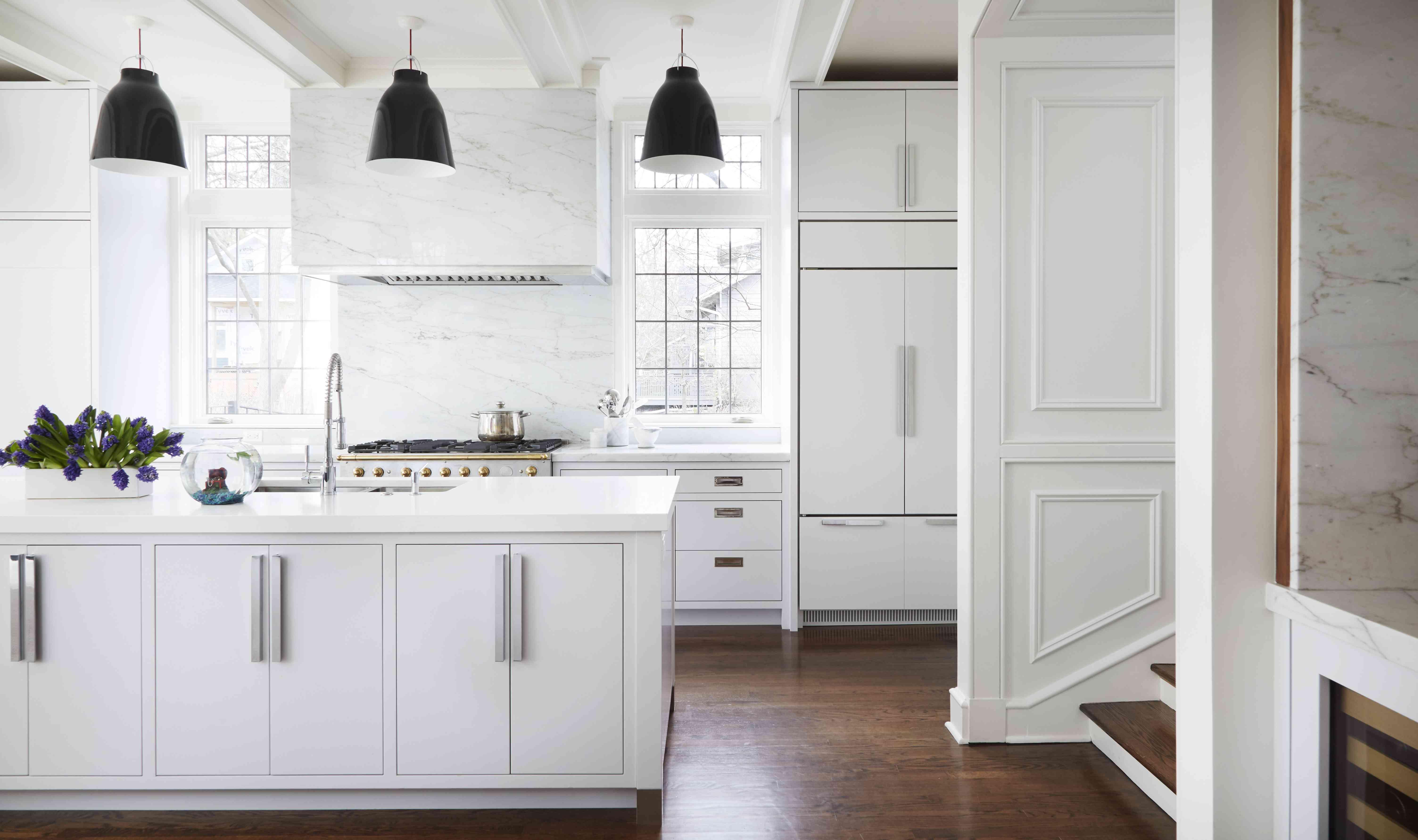 Muebles blancos elegantes y placa para salpicaduras de mármol en la cocina moderna