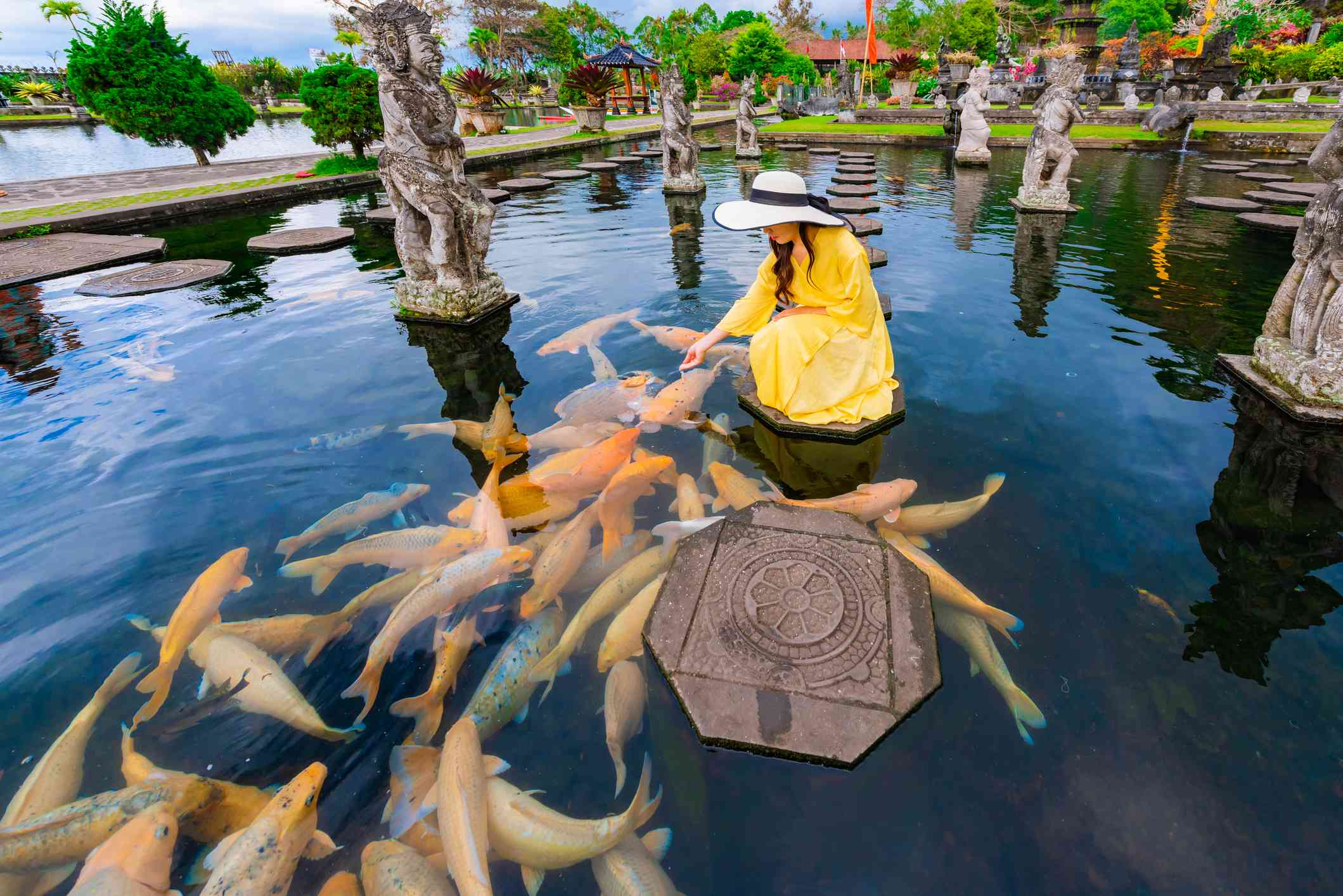 A woman feeding koi fish in a pond full of sculptures.