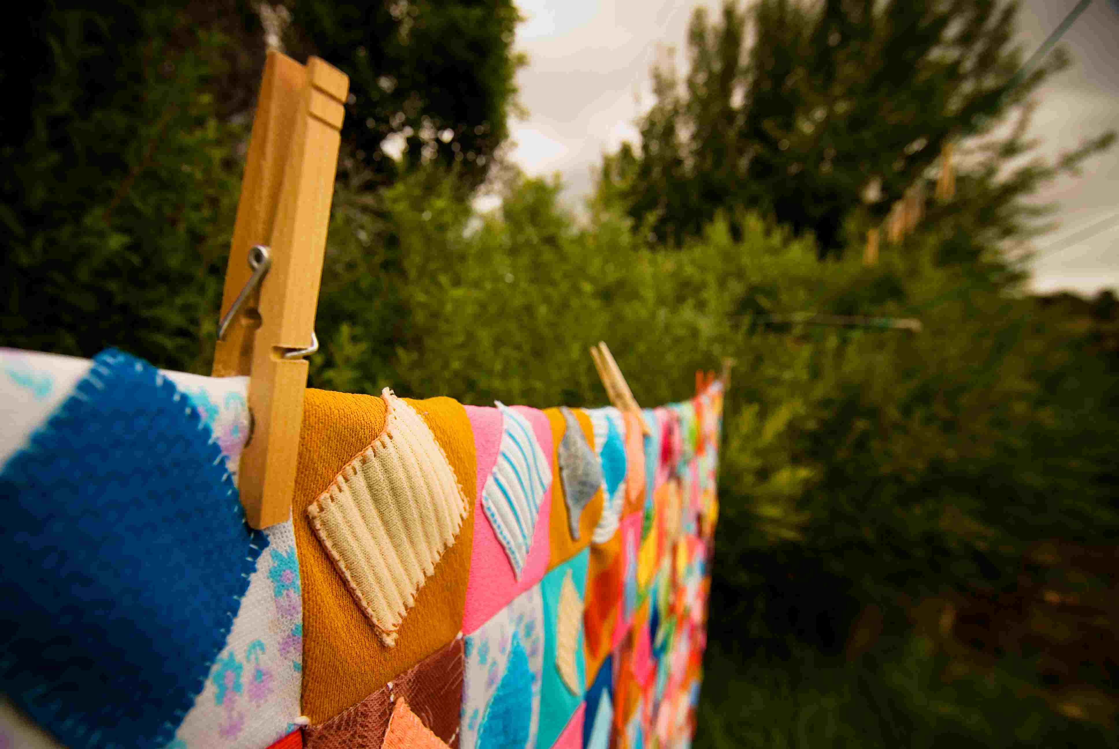 A colorful quilt on a clothesline