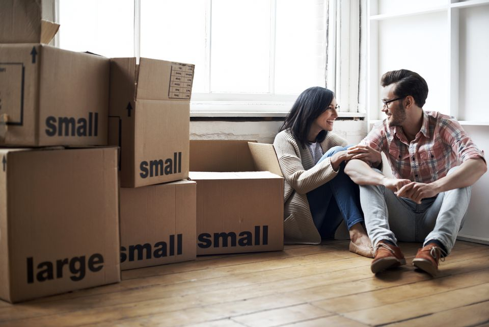 Couple sitting on the floor surrounded by packed moving boxes