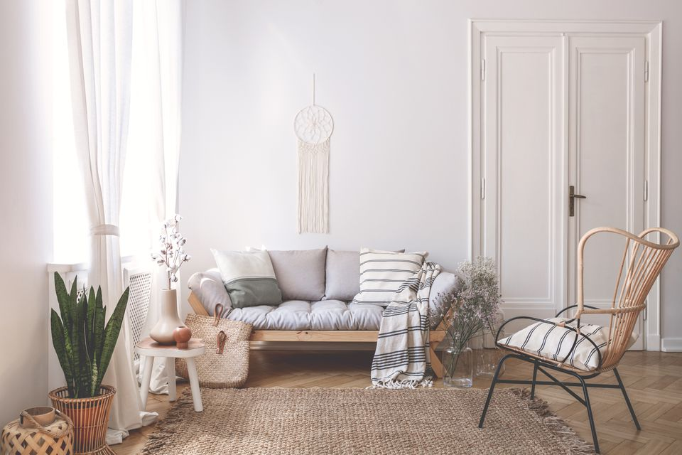 Wooden sofa with cushions in white living room interior with plant and armchair. Real photo