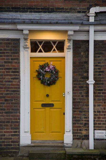 Una cálida puerta de color amarillo anaranjado en una casa de ladrillo con molduras blancas