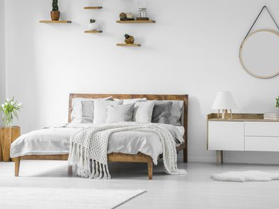 Comfortable big wooden framed bed with linen, pillows and blanket, nightstand beside and round mirror hanging on a white wall in a bright bedroom interior.