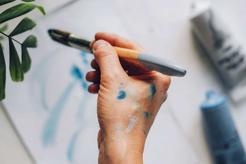 Paint on skin while holding paintbrush above white paper with blue paint