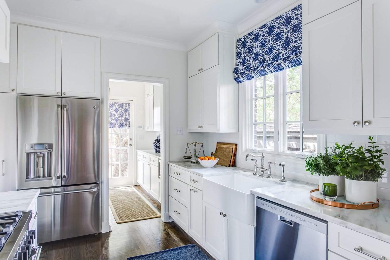 cocina blanca con vigas de madera, isla azul claro, y acentos de cobre y oro