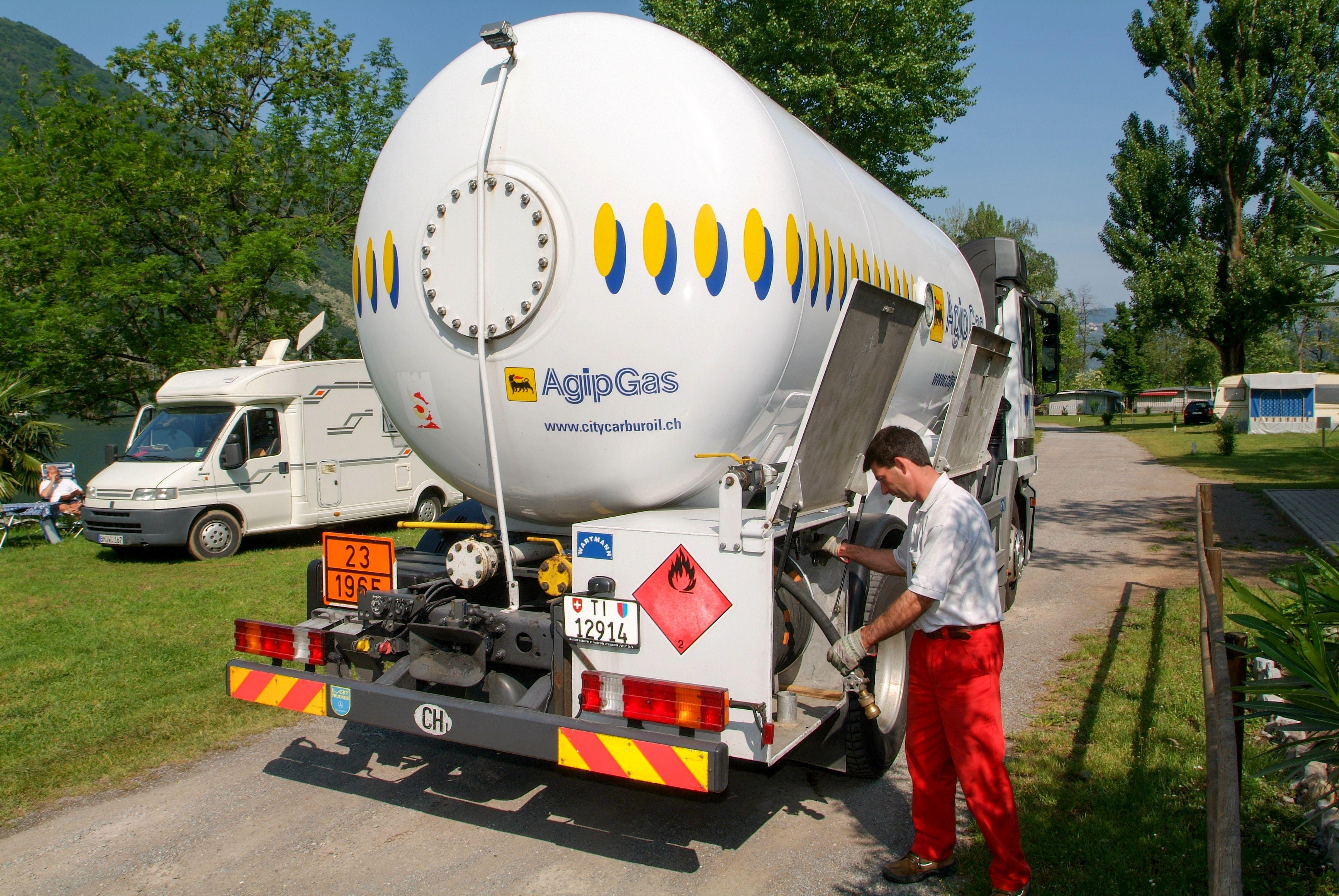 Trabajador que abastece de gas en un tanque en el jardín