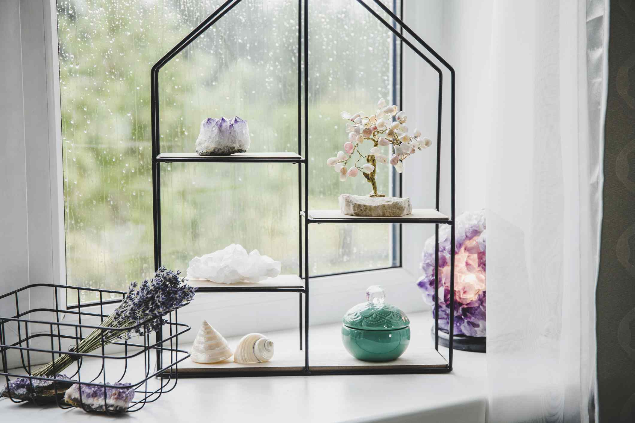 Minimal still life with modern metal wire and wooden shelf on window sill for home decoration. Spiritual interior ,semi precious gemstones on display.